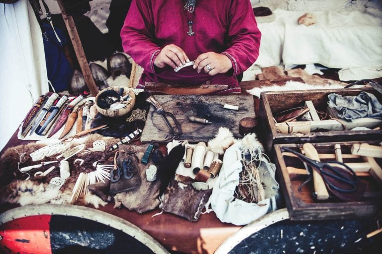 Awl for leather stitching in front of lady with many other goods for sale