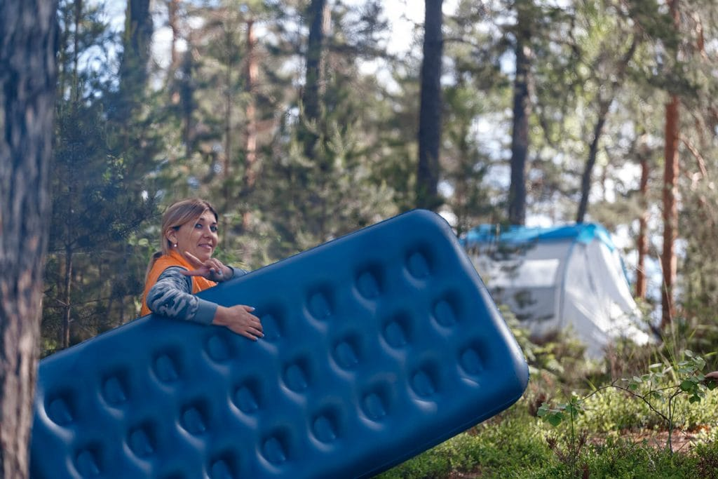 Camper carries blue air mattress fully pumped to tent out in the wilderness