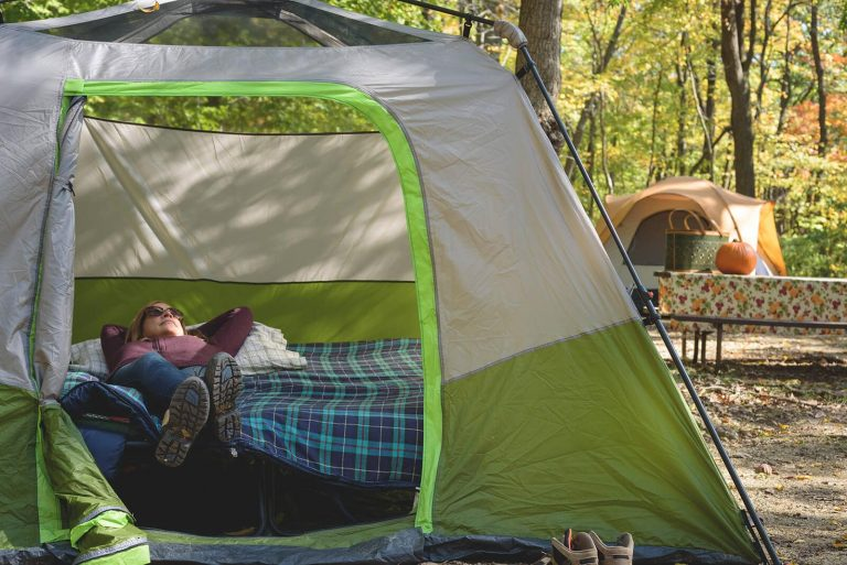 Camper happily lying on tent cot offgroun in two person tent in summer campground