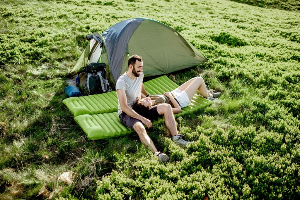 Couple camping on grass laying on Green airmattress