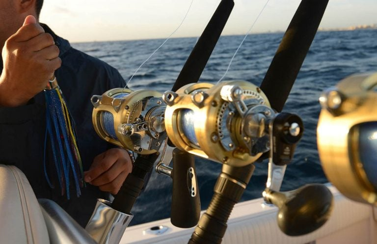 Fisherman with three gold saltwater spinning fishing reels on boat sea