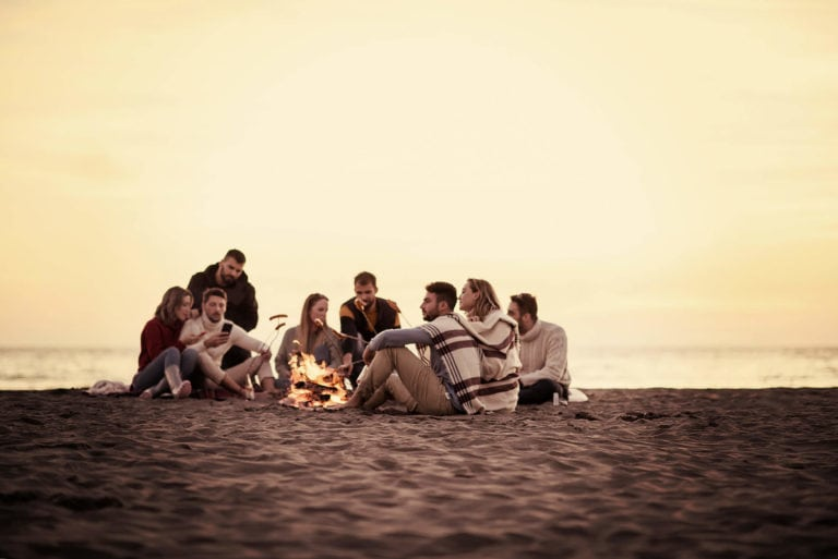 Group of young beach campers cooking on an opern fire