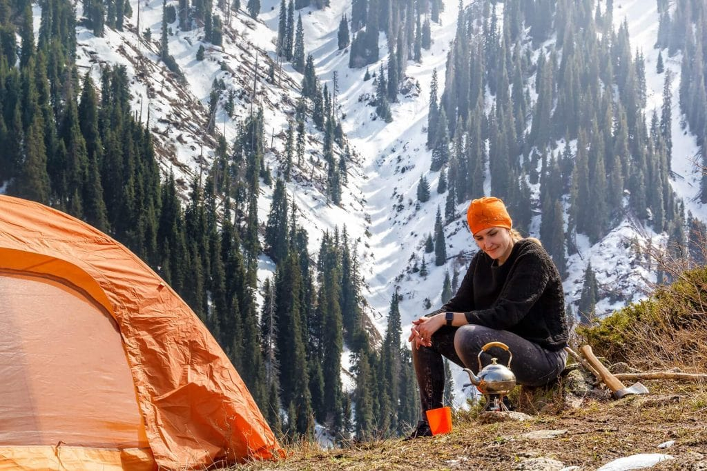 Lone camper prepping morning instant coffee while camping snow capped mountains