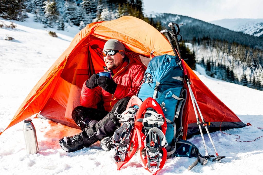 Male camper sitting in hot warm tent in snow morning light ready for adventure