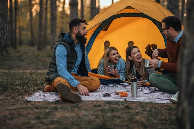 Pair of campers in happy comfortable setting after arriving at campsite