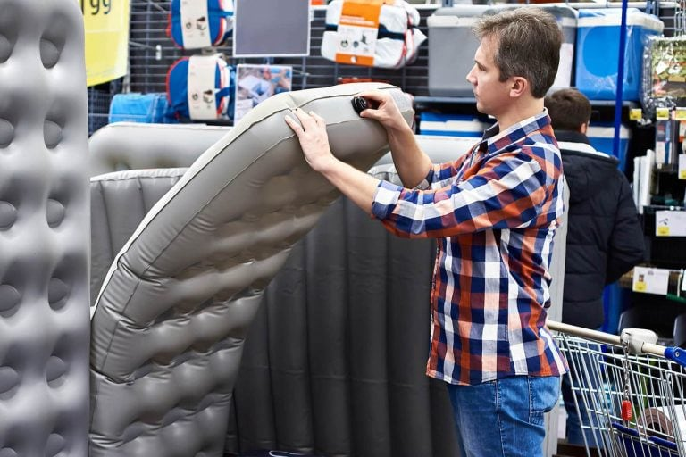 Shopper in camping store looking at air mattresses
