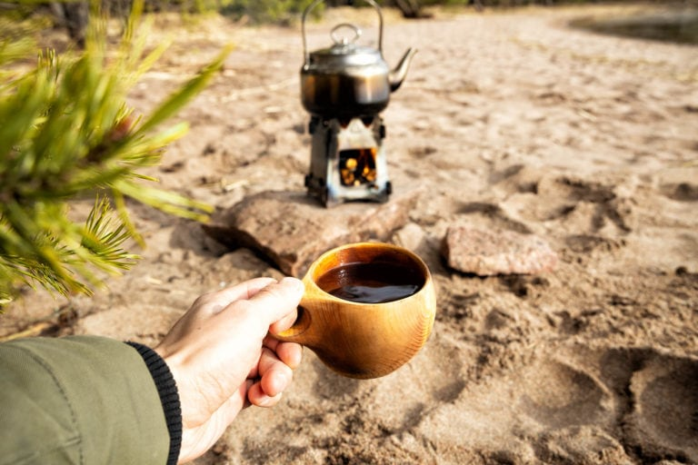 Small woodburning stove with hot cup of coffee while camping