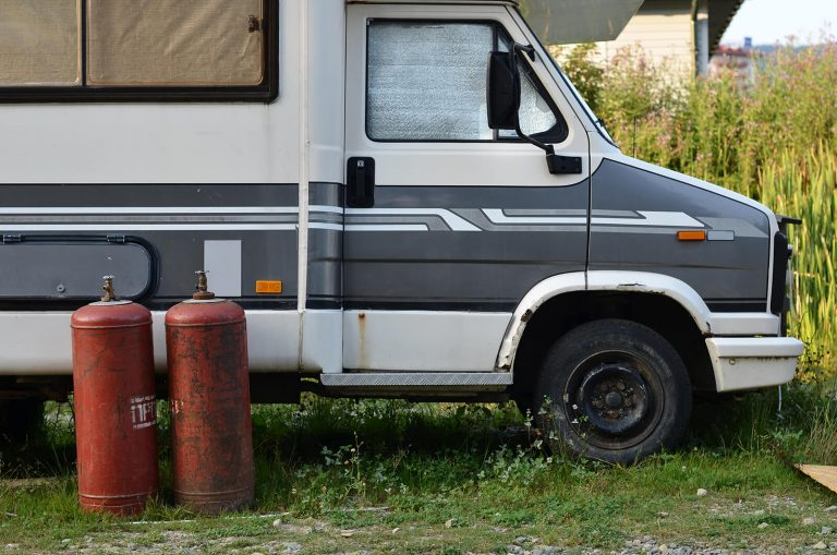 Two red propane cylinders stood in front of a parked grey striped and white campervan side profile 1600x1060