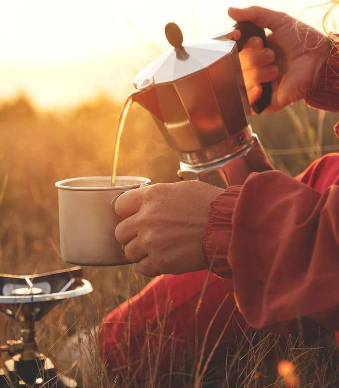 Camper in morning light pouring camping coffee