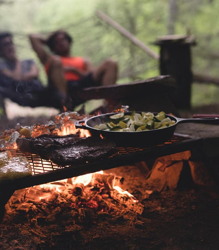 Two campers watch on as campfire cooks various foods on campfire embers