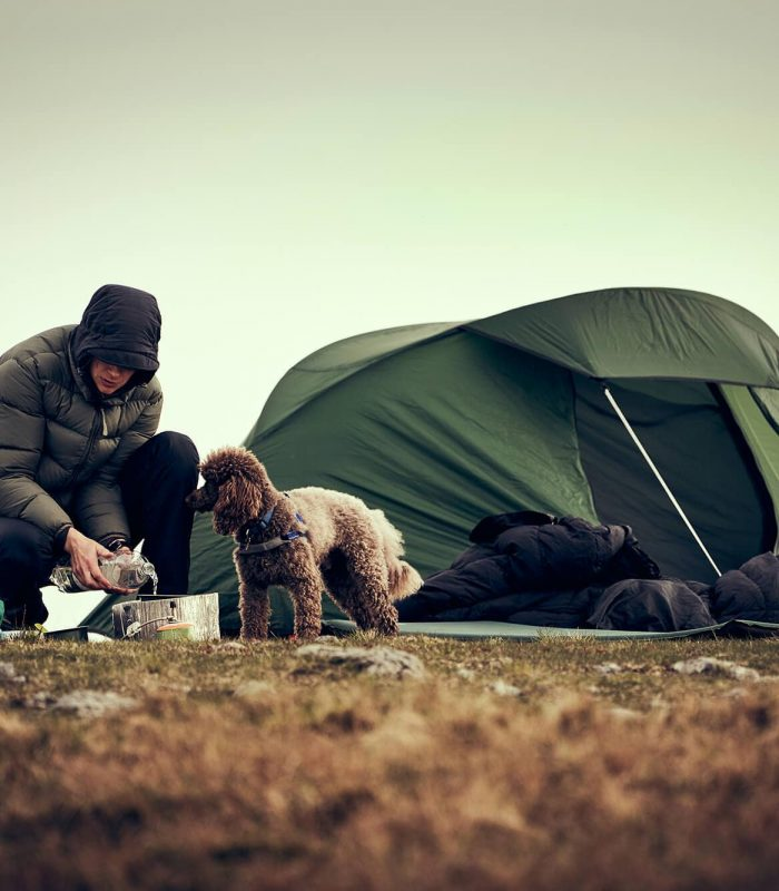 Hiker and canine companion getting tent warm and ready in winter camping location