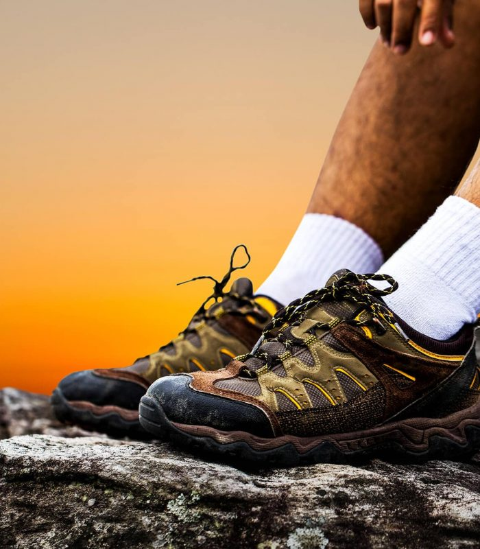 Man resting on rocky cliff with hiking boots and sock liners