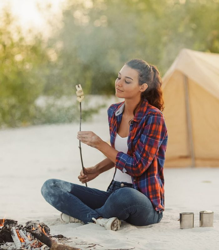 Young woman solo camping cooking snacks on campfire, on beach in front of cream coloured tent