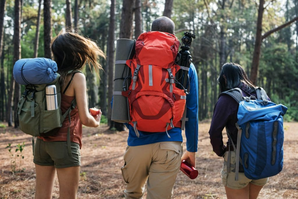 A group of three campers walking with backpacks gear