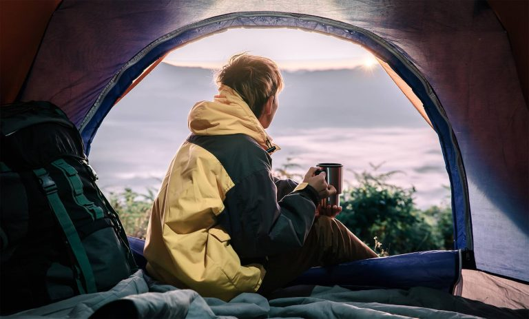 male camper gazes out of morning winter tent thinking of the best tent heaters